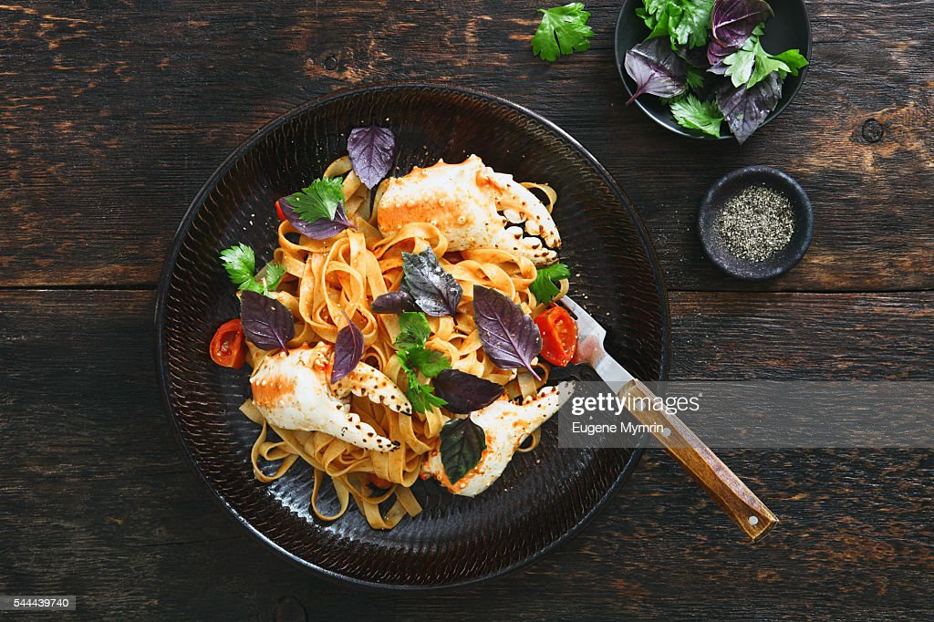 Pasta with crab claws, cherry tomato and herbs : Stock Photo