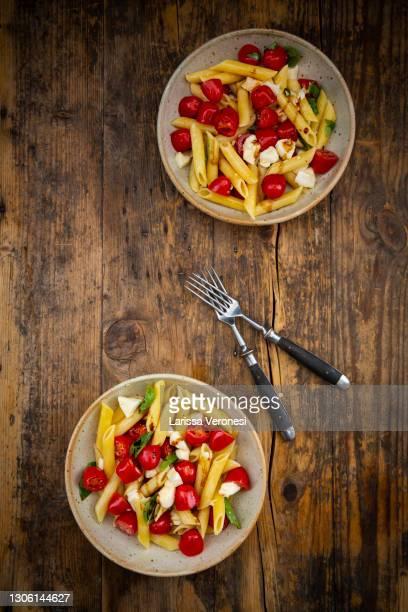 pasta with tomatoes, mozzarella, and basil - larissa veronesi stock-fotos und bilder