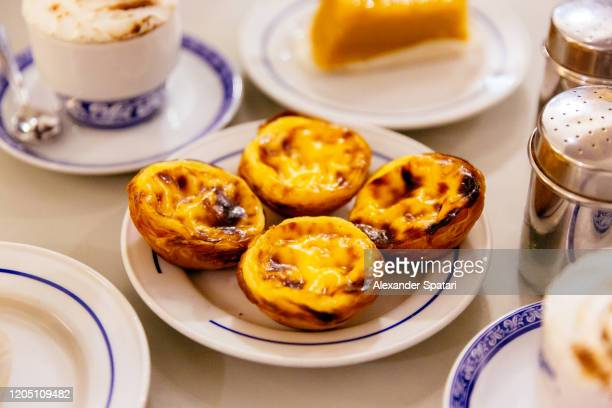 pasteis de nata, traditional portuguese pastry on a plate - lissabon stock-fotos und bilder
