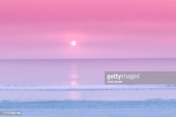 pastel colored sunrise over the ocean - pink sky stock pictures, royalty-free photos & images