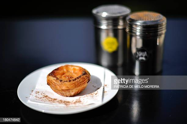 A 'Pastel de nata' Lisbon's typical pastry is displayed next to a sprinkler from the brand Nata at the Nata's Cafe in Lisbon on August 10 2012 Under...