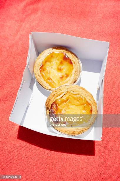 pastel de natas in a box on red tablecloth, typical portuguese tarts - traditionally portuguese stock pictures, royalty-free photos & images