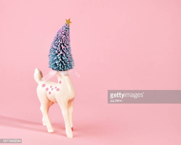 Pastel holiday scene with deer figure with Christmas tree head on pink background.