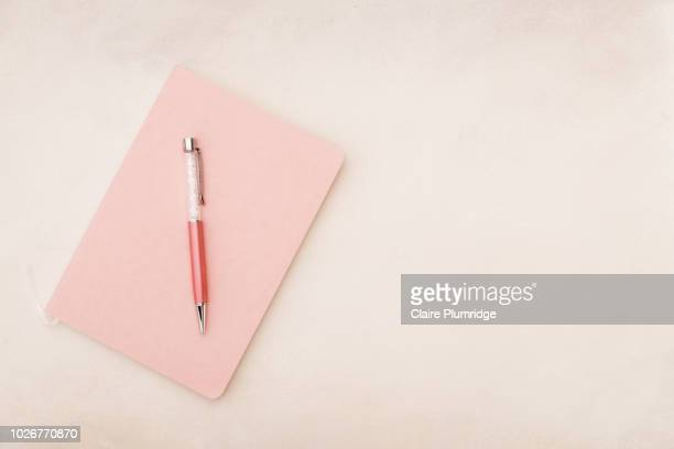 pastel - overhead view, styled stock image of pink coloured notebook on a pink background - pen stock pictures, royalty-free photos & images