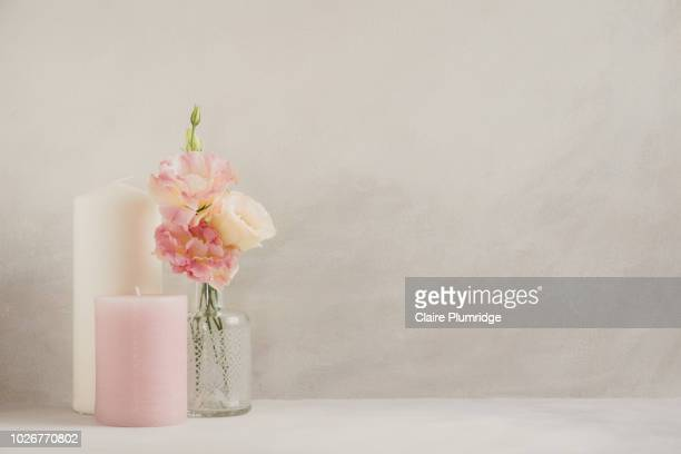 pastel - pretty styled stock image of pink/cream coloured lisianthus in a little glass vase and two candles against a watercolour effect grey background. - weiblichkeit stock-fotos und bilder