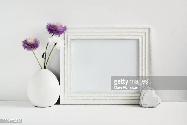 pastel - styled stock frame mock-up image with purple and white stokes asters in a white vase next to a blank white frame. - weiblichkeit stock-fotos und bilder