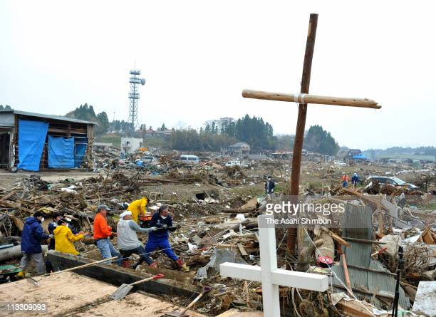 A pastor and volunteer workers clear the debris around the cross made by logs washed away by the tsunami at the place where the Kesennuma Daiichi...