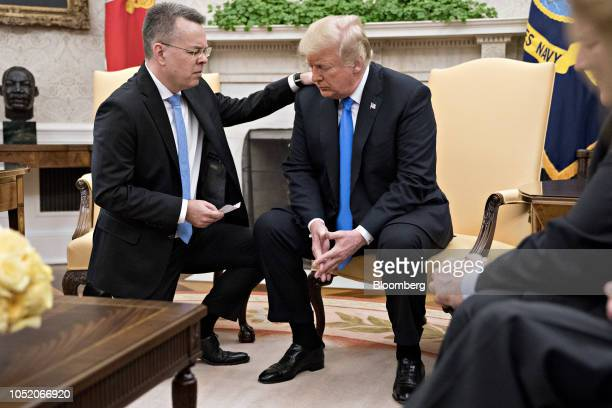 US Pastor Andrew Brunson left prays with US President Donald Trump during a meeting in the Oval Office of the White House in Washington DC US on...