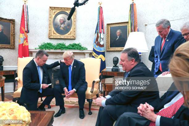 US pastor Andrew Brunson prays for US President Donald Trump as they meet in the Oval Office of the White House in Washington DC October 13 2018...