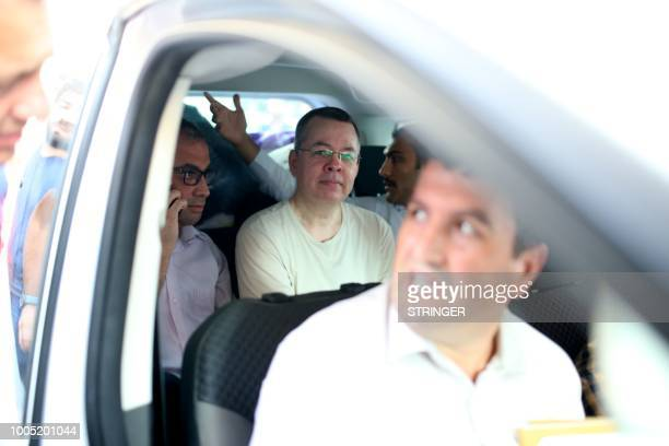 US Pastor Andrew Craig Brunson is seen inside a car escorted by Turkish plain clothes police officers as he arrives at his house on July 25 2018 in...