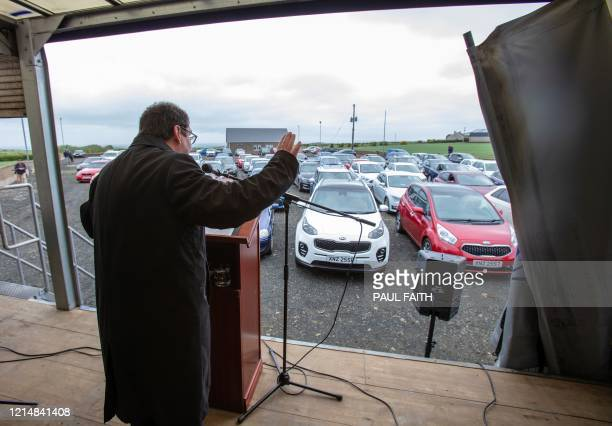 Pastor Billy Jones stands inside a potato delivery lorry as he delivers his sermon to his parishioners sat inside their cars to social distance in...