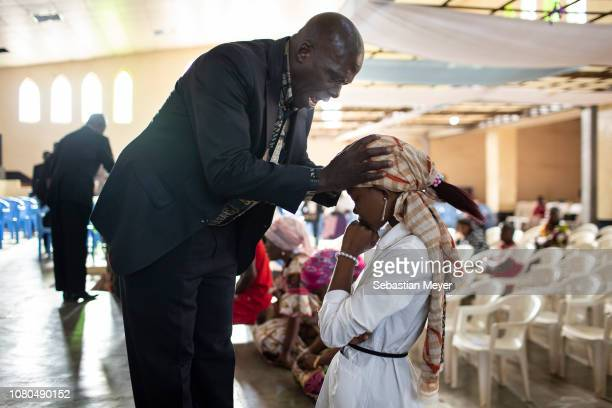 A pastor blesses a parishioner at the Temple Evangélique de Carmel in central Kolwezi Kolwezi is a mining town that is experiencing a boom thanks to...