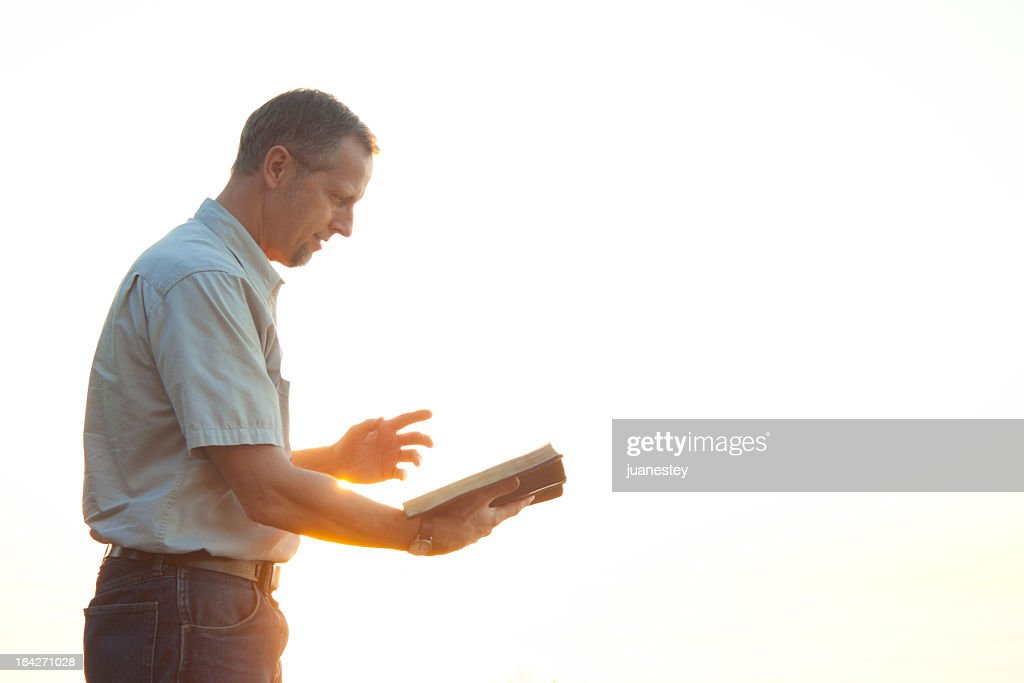 Pastor casually dressed walking in sunlight reading Bible : Stock Photo