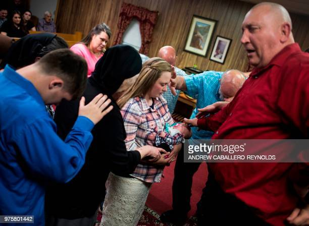 Pastor Chris Wolford and members of his church pray for a new born baby during a Pentecostal serpent handlers service at the House of the Lord Jesus...
