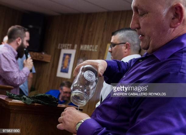 Pastor Chris Wolford pours strychnine into a cup during a Pentecostal serpent handlers service at the House of the Lord Jesus church in Squire West...