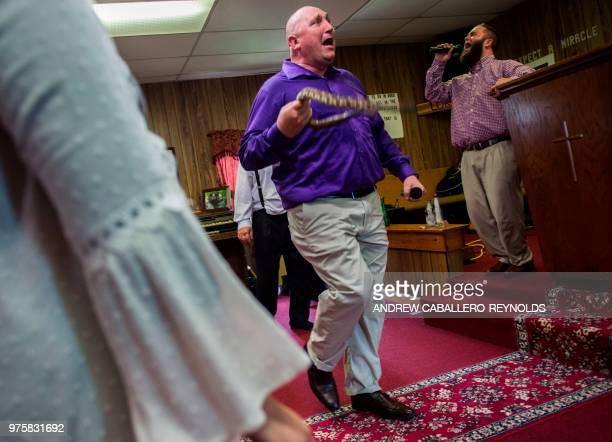 Pastor Chris Wolford sings as he holds a tiber rattlesnake during a Pentecostal serpent handlers service at the House of the Lord Jesus church in...