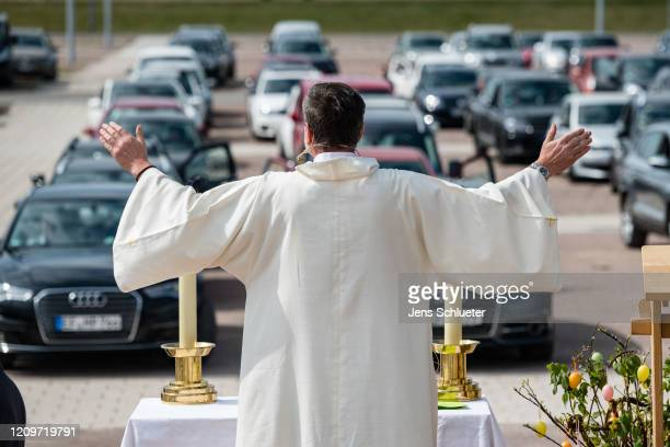 Pastor Christoph Knoll from the Erfurt Thomas community gives the blessing while people sit in their cars as they attend an Easter Sunday religious...