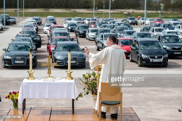 Pastor Christoph Knoll from the Erfurt Thomas community speaks during a sermon while people sit in their cars as they attend an Easter Sunday...