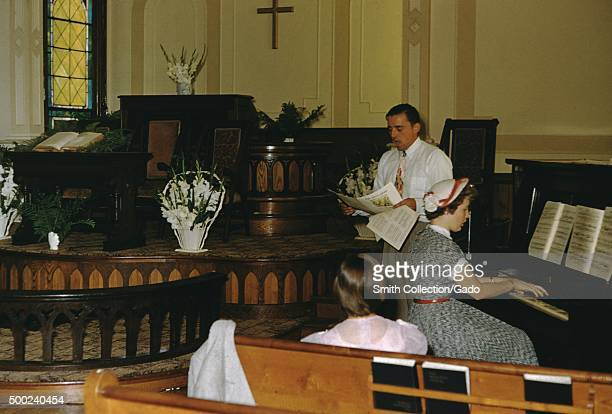 Pastor female organist and churchgoer signing hymns the organist and pastor in mid song the pastor holding a piece of sheet music the organist...