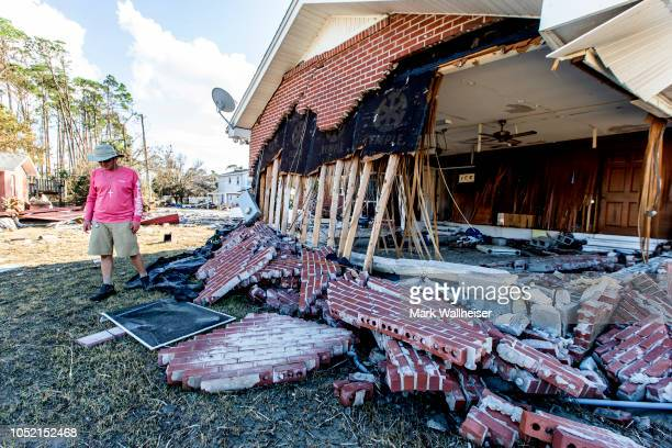 Pastor Geoffrey Lentzs past his damaged home next to the First United Methodist Church after their home was gutted by the storm surge fromHurricane...