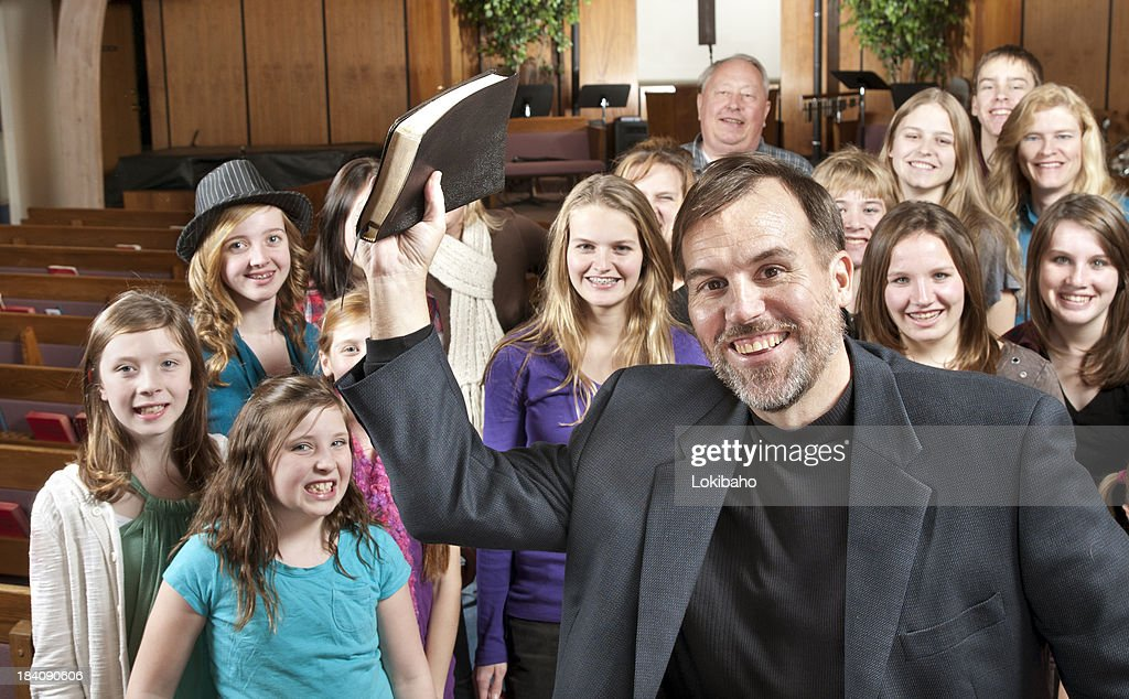 Pastor holding Bible with His People Behind : Stock Photo
