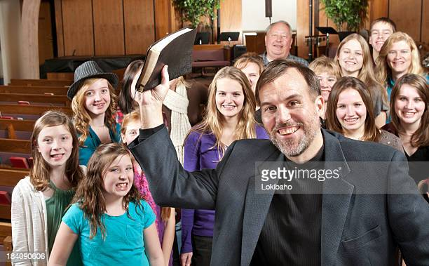 pastor de retención de la biblia con su pueblo detrás - congregación fotografías e imágenes de stock