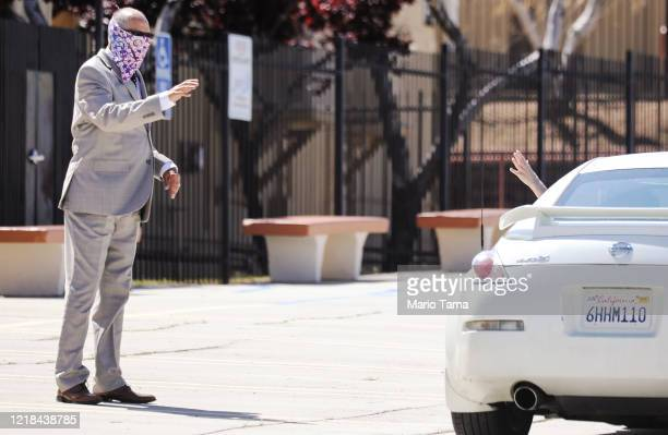 Pastor Jerel Hagerman waves to a departing congregant after conducting a drivein 'car church' Easter service in the parking lot of Joshua Springs...