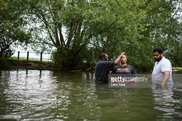 Pastor Julian D'Oyley of the Apostolic Faith Church, associated with United Pentecostal Church prays with Esther Applewhite after baptising her in...