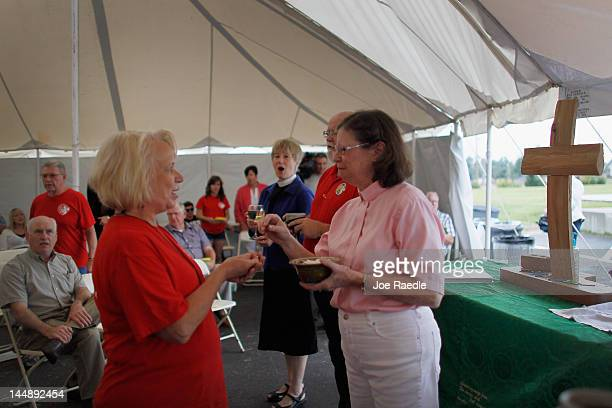 Pastor Kathy Redpath gives communion during a service in a temporary tent set up by the Peace Lutheran Church next to their church that that was...