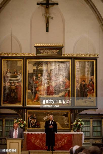 A pastor leads a service in the Stadtkirche Sankt Marien church to commemorate the 500th anniversary of Luther's nailing of his 95 theses on the...