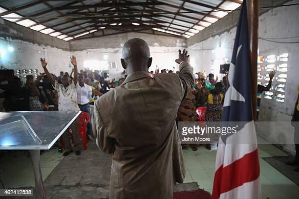 Pastor leads his congregation in prayer during a Sunday service at the Bethel World Outreach Church in the West Point township on January 25, 2015 in...