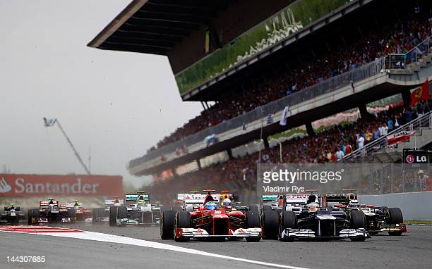Pastor Maldonado of Venezuela and Williams and Fernando Alonso of Spain and Ferrari drive side by side after the start of the Spanish Formula One...