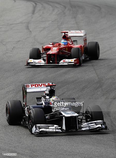 Pastor Maldonado of Venezuela and Williams holds off the challenge of Fernando Alonso of Spain and Ferrari on his way to winning the Spanish Formula...
