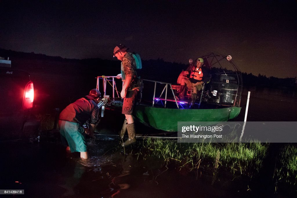 Pastor Marty Murray, piloting the boat, and his group of volunteers tie their boat back to their truck after hobbling back because their exhaust pipe and rudder broke. They ended up picking up a 22-year-old who was visiting a friend because his mother became worried and called him in to be rescued.