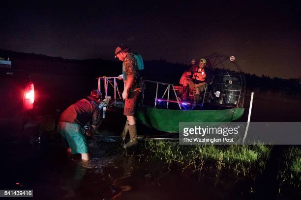 Pastor Marty Murray piloting the boat and his group of volunteers tie their boat back to their truck after hobbling back because their exhaust pipe...