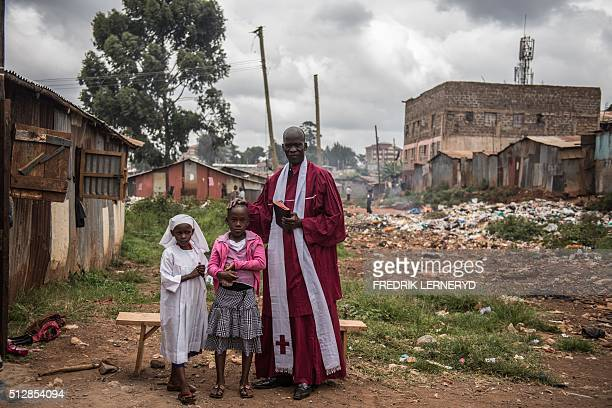 Pastor Peter Jaleny poses with two younger members of his church outside the home of newborn twin girls Bridget Lillian and Brillian Mary prior to a...