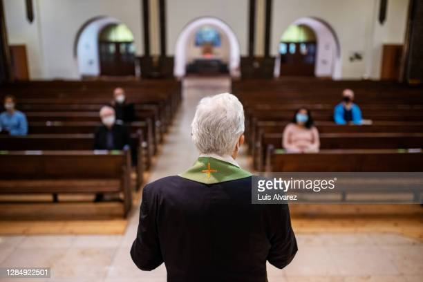 pastor praying for congregation - pastor stock pictures, royalty-free photos & images