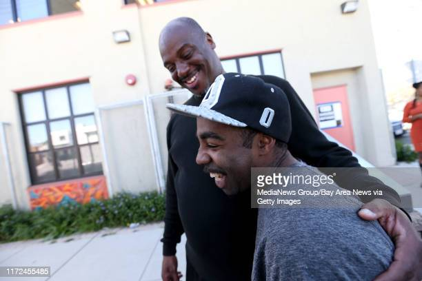 Pastor Raymond Lankford left cheers up Bobby Bishop outside a temporary American Red Cross shelter setup at the West Oakland Youth Center in Oakland...