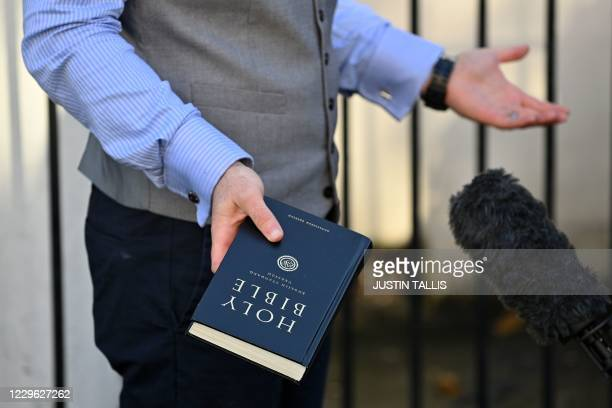 Pastor Regan King, of the Angel church in north London gives an interview as he holds a Holy Bible outside the church on November 15, 2020. - An...