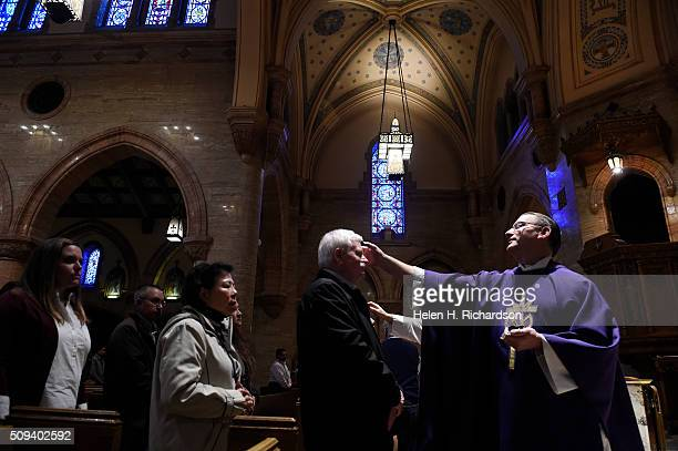 Pastor Reverend Christopher Uhl right puts ashes on the foreheads of parishioners after Ash Wednesday mass at Holy Ghost Catholic Church on February...