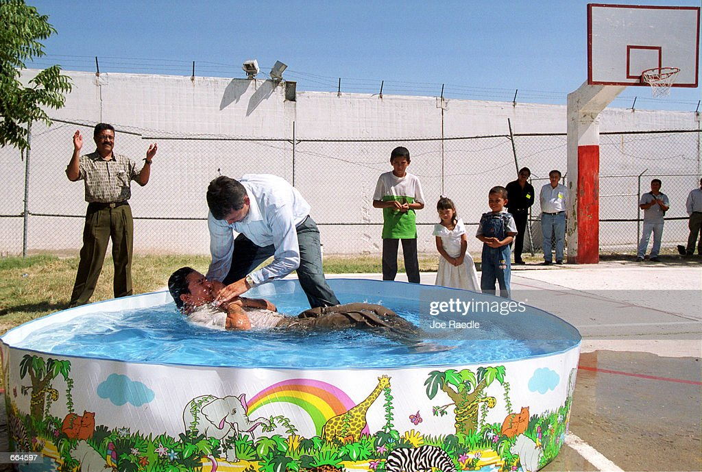 Pastor Victor Toro Gomez conducts a baptism inside a prison October 2, 2000 at Ciudad Juarez, Mexico. The pastor, a former inmate, baptised 12 other prisoners in the swimming pool. (Photo by Joe Raedle/Newsmakers) TO