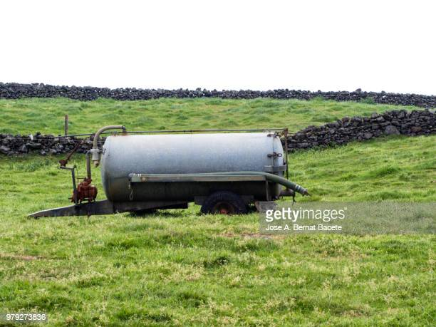 pastoral landscape, tank metallic to drink the cattle over pastures green separated by stone walls. terceira island in the azores islands, portugal. - storage tank stock photos and pictures