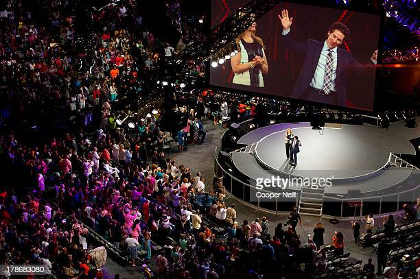 Pastors Victoria Osteen and Joel Osteen speak during MegaFest at the American Airlines Center on August 30 2013 in Dallas Texas