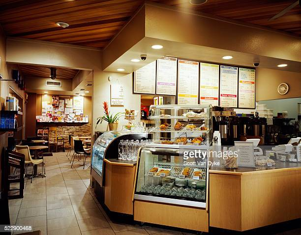 pastries are displayed near the counter of a coffee shop - image stock pictures, royalty-free photos & images
