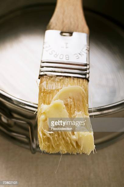 pastry brush with butter in front of baking tin - basting brush stock photos and pictures