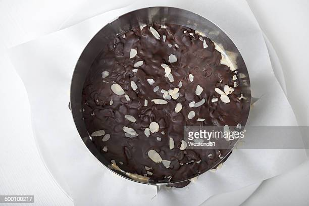 Pastry case with sliced almonds and dark chocolate in cake ring, elevated view