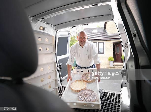 pastry chef loading cakes into van - bestelwagen stockfoto's en -beelden