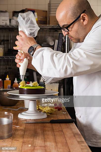 Pastry chef piping a cake