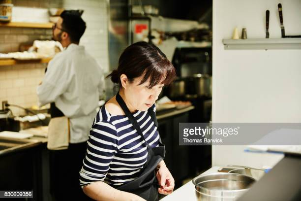 Pastry chef preparing for evening service in restaurant kitchen