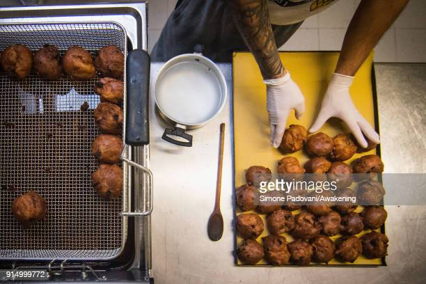 A pastry chef puts the Frittelle a typical sweet of Venetian carnival on a tray to cool in Costantini laboratory on February 6 2018 in Venice Italy...